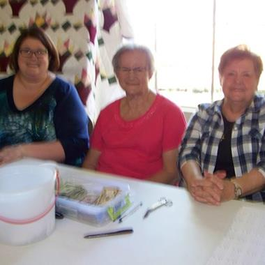 A terrible photo of 3 lovely ladies and the gorgeous Marian Council quilt